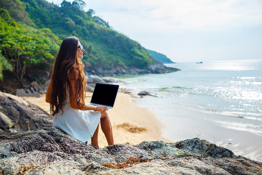 brunette woman sitting on the rock with laptop near  sea
