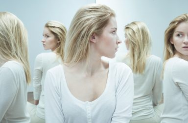Shot of a young woman dressed in white looking back with anxiety at her reflections in the mirror