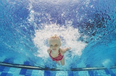 Baby girl swimming underwater and diving in pool with fun - jumping deep down with splashes Active lifestyle water sports activity and exercising with parents during summer family vacation with child